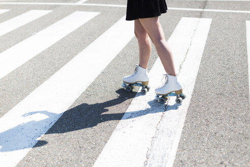 Young woman with roller skates on zebra crossing, partial view - JPF00249