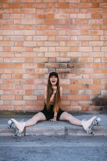Portrait of laughing young woman  with roller skates sitting on sidewalk - JPF00252