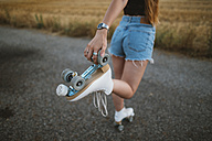 Young woman with roller skates on country road, partial view - JPF00255