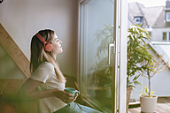 Young woman relaxing at home with a cup of tea, listening music - GUSF00096