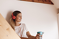 Young woman relaxing at home with a cup of tea, listening music - GUSF00108