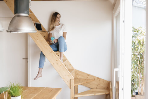 Young woman sitting on wooden stairs, using laptop - GUSF00126