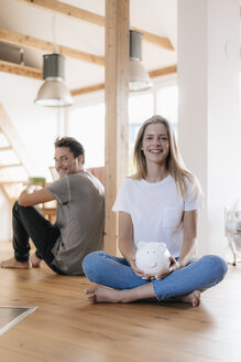 Couple sitting in new home with a piggy bank - GUSF00135