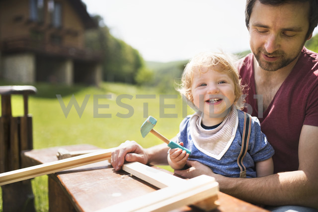 Father and little son working with hammer in garden - HAPF01996
