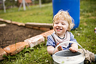 Boy in garden playing with watering can - HAPF02002