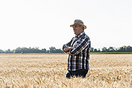 Smiling senior farmer standing in a field - UUF11165