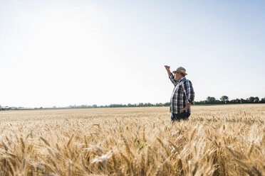 Senior farmer standing in wheat field looking at distance - UUF11168