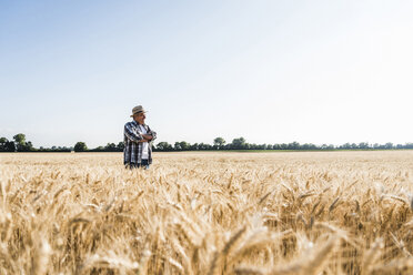 Happy senior farmer standing in wheat field - UUF11177
