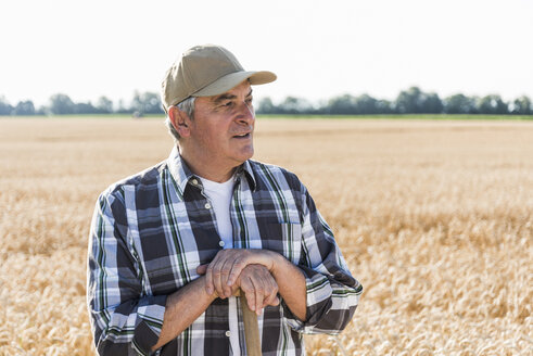 Portrait of senior farmer standing in front of a field looking at distance - UUF11180