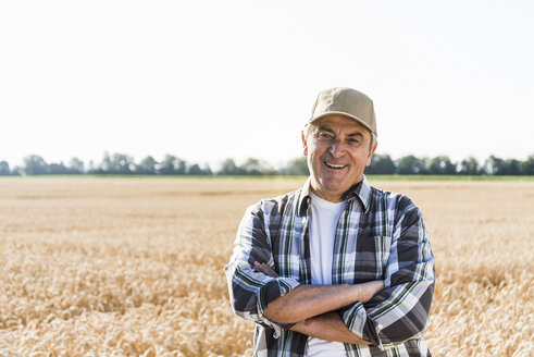 Portrait of laughing senior farmer standing in front of a field - UUF11183