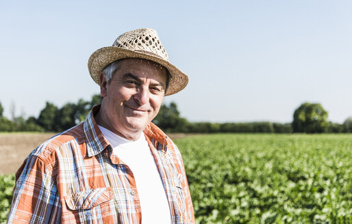 Portrait of content senior farmer standing in front of a field - UUF11204