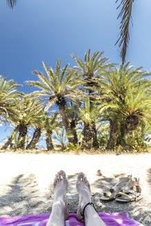 Greece, Crete, Vai, feet of woman relaxing on the beach - CHPF00414