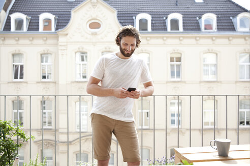 Smiling man standing on balcony looking at cell phone - MFRF00883