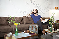 Portrait of young man on the phone sitting on couch in a coffee shop with book - MFRF00898