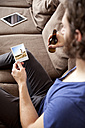 Man sitting on couch with beer bottle looking at instant photo - MFRF00901