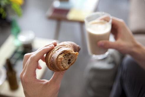 Man's hands holding croissant and  glass of Latte Macchiato - MFRF00907