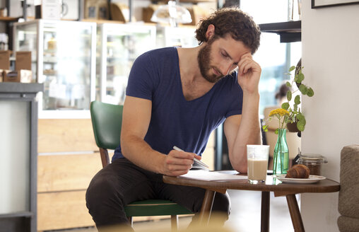 Pensive young man sitting in a coffee shop writing letter - MFRF00913