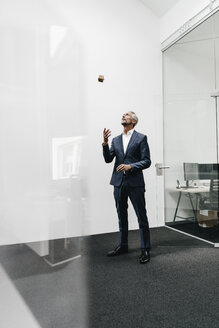 Mature businessman in office throwing up Rubik's Cube - KNSF02115