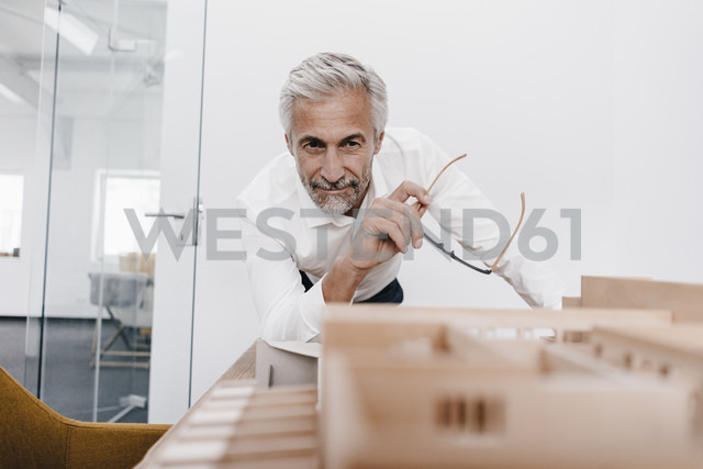 Mature businessman examining architectural model in office - KNSF02118