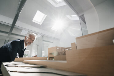Mature businessman examining architectural model in office - KNSF02124