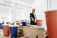 Mature businessman with architectural model in office throwing a ball - KNSF02130