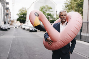 Mature businessman on the street with inflatable flamingo - KNSF02136