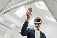 Mature businessman in office wearing VR glasses holding Rubik's Cube - KNSF02142