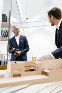 Two businessmen with architectural model in office - KNSF02145