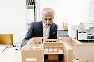 Mature businessman examining architectural model in office - KNSF02148