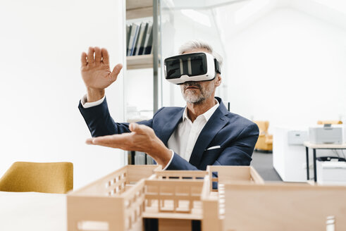 Mature businessman with architectural model in office wearing VR glasses - KNSF02154