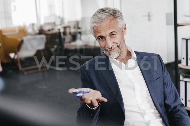 Portrait of mature businessman in office with fidget spinner - KNSF02157 - Kniel Synnatzschke/Westend61
