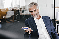 Portrait of mature businessman in office with fidget spinner - KNSF02157