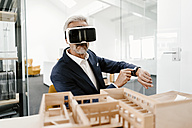 Mature businessman with architectural model in office wearing VR glasses - KNSF02160