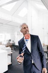 Mature businessman in office receiving an uppercut - KNSF02166