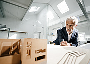 Mature businessman examining architectural model in office - KNSF02172