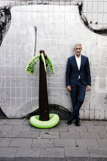 Mature businessman outdoors with inflatable palm tree - KNSF02181