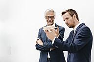 Two businessmen examining architectural model - KNSF02184