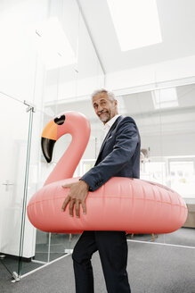 Businessman in office with inflatable flamingo - KNSF02190