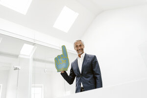 Smiling mature businessman holding toy hand in office - KNSF02205
