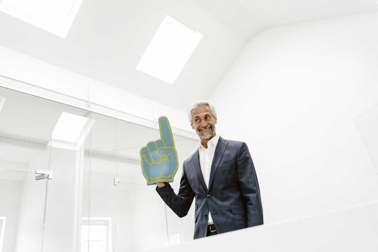Smiling mature businessman holding toy hand in office - KNSF02205 - Kniel Synnatzschke/Westend61