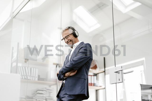Happy mature businessman in office wearing headphones - KNSF02208