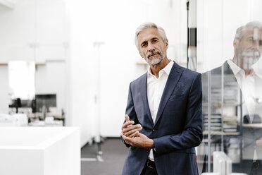 Portrait of confident mature businessman in office - KNSF02220