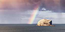 UK, Scotland, North Berwick, Firth of Forth, view of Bass Rock with rainbow and storm clouds - SMAF00777