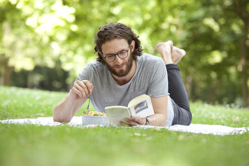 Man reading book on blanket in a park while eating noodle salad - MFRF00917