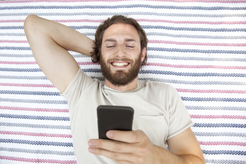 Portrait of smiling man lying on blanket in a park using cell phone, top view - MFRF00932