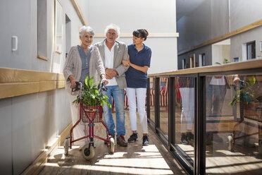 Gereatric nurse helping senior man and woman to walk down corridor - ZEF14224