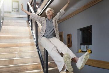 Happy senior woman sliding down a staircase - ZEF14227