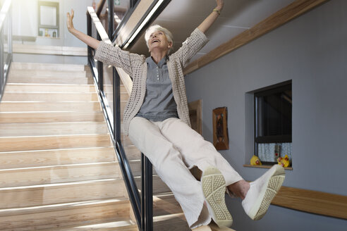 Happy senior woman sliding down a staircase - ZEF14227
