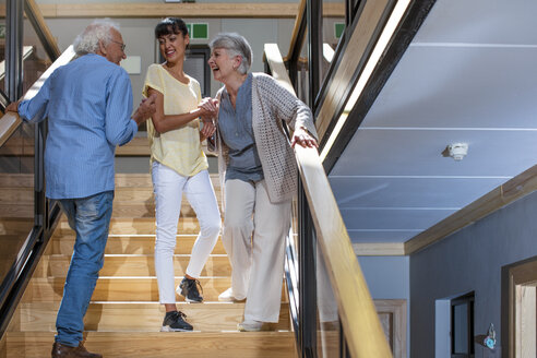 Nurse helping laughing seniors on staircase - ZEF14230
