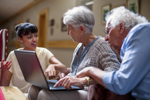Nurse teaching seniors in retirement home, how to use laptop - ZEF14233